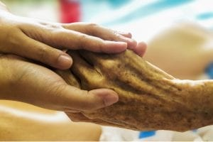 palliative care patient holding hand of loved one