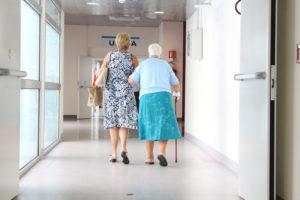 volunteer walking elderly woman down hallway